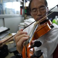 Silken tones: Professor Shigeyoshi Osaki plays a violin strung with spider-silk strings. | TOMOKO OTAKE PHOTO
