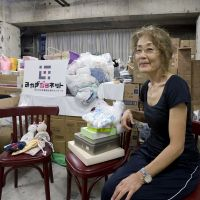 Yuko Kusano, cofounder of the NPO Miyagi-Jonet, sits in a storeroom in Sendai filled with emergency and other supplies for women left homeless by the March earthquake and tsunami. | ROB GILHOOLY PHOTOS