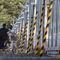 A woman walks her bicycle through a temporary housing district in Natori, Miyagi Prefecture, in early September.