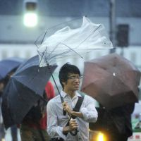 Wild times: A brolly expires as Typhoon Roke hits central Tokyo on Sept. 21. | KYODO PHOTO