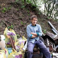 Poet Stephen Gill sits amid refuse collected from Mount Ogura in western Kyoto suburb during a cleanup operation in early October. | JANE SINGER PHOTOS
