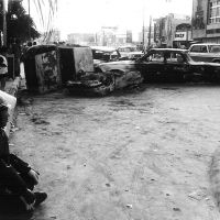 Aftermath of disturbances: As he sits on the curb, an Okinawan policeman surveys wreckage following rioting on Dec. 20, 1970, in what is now the city of Okinawa. | COURTESY OF LARRY GRAY