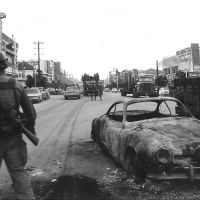 A U.S. serviceman stands next to a charred vehicle on a city street.
