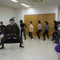 All together now: Students in a recent kabuki-themed workout workshop given by kabuki actor Nakamura Hashigo (left) in the Tsukiji district of central Tokyo, practice the hakowari position, one of the basic moves in the traditional theatrical art. | TOMOKO OTAKE PHOTOS