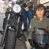 Their word against the law's: Jian Macdonald, now 9, poses on the bike that he and his father, Todd, allege was vandalized by a nightstick-wielding police officer during an argument outside the Marui department store in Senju, in Tokyo's Adachi Ward, on Oct. 29. Jian and Todd say the officer punched Jian in the shoulder and shook him violently when he tried to take a cellphone video of the altercation between his father and the officer, during which the bike's front fender was apparently broken. | SIMON SCOTT