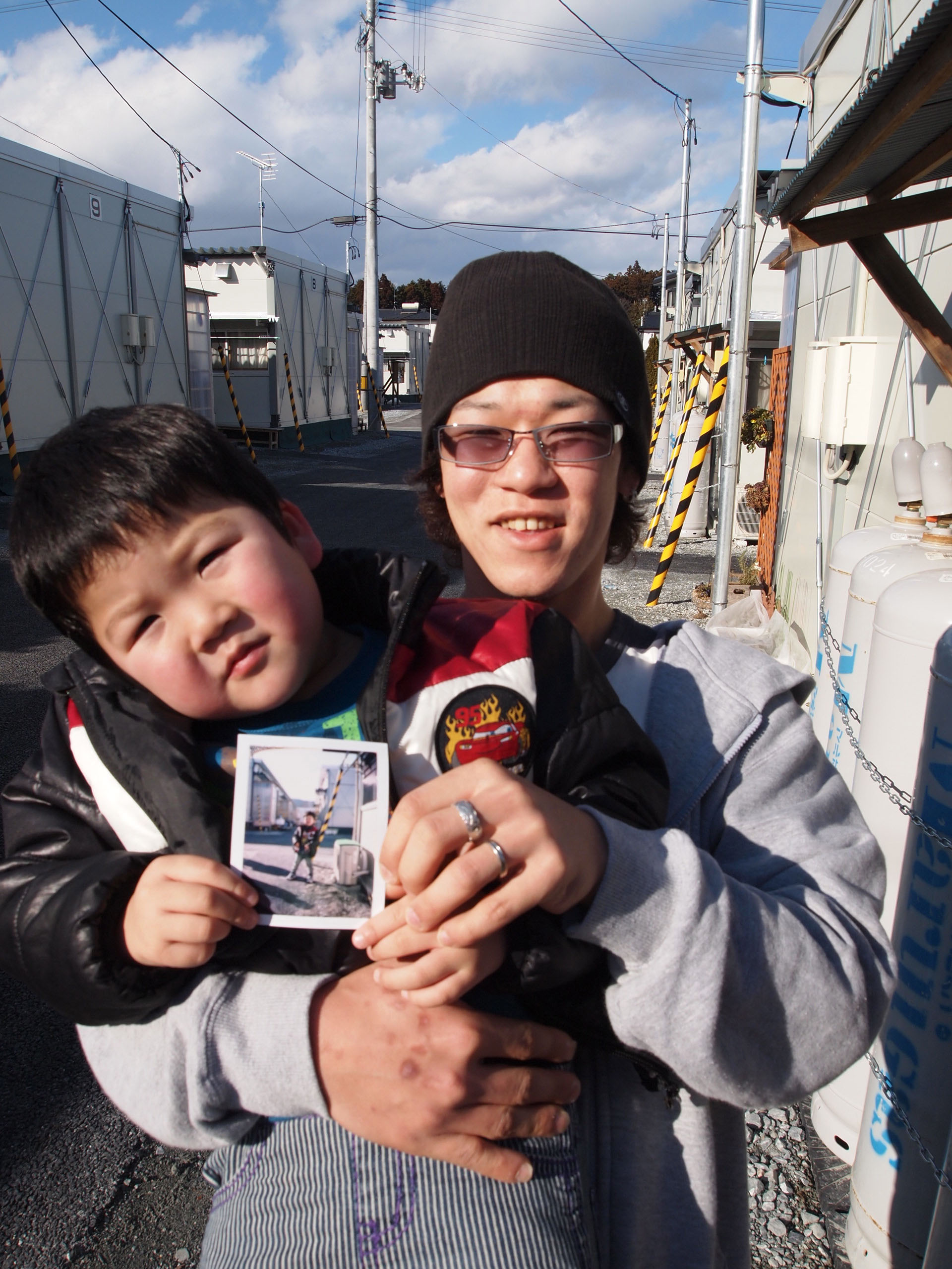 Memory bank: Proud father Tomohiro Nagakura shows off his son, Yushin, and a photo given to him by Photohoku at the Hirobata Temporary Housing Complex in Shinchi, Fukushima Prefecture. | JON MITCHELL PHOTOS
