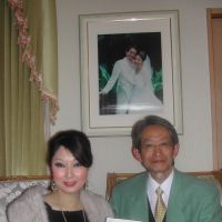 Tales from the south: Yoichi Kubota and Patmakorn Suntharothok, who is holding 'More Than Love at Yala,' a novel that she recently had published, sit in front of their wedding photo at their house in Saitama. | MAMI MARUKO