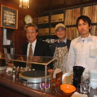 The beat goes on: Masataka Yusa (left), who heads the Chigusa Kai supporters group, with two staff members and some of the cafe's more than 3,000 records. | ERIKO ARITA PHOTOS