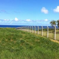 Keep out: A fence topped with razor-wire separates the U.S. Iejima Island Auxiliary Airfield (right) from Japan. | JON MITCHELL