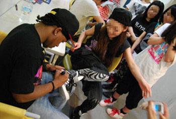 Suspect: James Blackston signs a shoe for a girl at a dance school in Sendai during a King Tight Workshop he taught two days before he and a 19-year-old fellow American allegedly met Nicola Furlong, who died in the early hours of May 24.