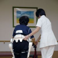 All together now: A nurse and a 'HAL for Wellbeing' assist a patient during ongoing trials of the robot suit in Japan. | YOSHIYUKI SANKAI, UNIVERSITY OF TSUKUBA / CYBERDYNE INC.