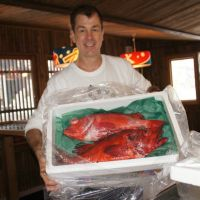 Catch of the day: James Gallagher poses with a box of menuke rockfish at his Ezo Seafood restaurant in the Niseko area of Hokkaido in February. | COURTESY OF JAMES GALLAGHER