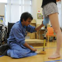 Perfect fit: Fumio Usui, a prosthetist at the Prosthetic and Orthotic Support Center, adjusts the artificial limb of one of his clients at the center in Tokyo's Arakawa Ward.