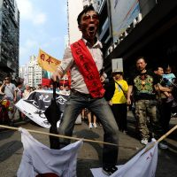 Such a little thing makes such a big difference: An activist stomps on Japanese flags during a demonstration over the disputed islets known as the Diaoyus in Chinese and the Senkakus in Japanese, as people make their way to the Japanese Consulate in Hong Kong for a spot of protesting Sunday over Japan's recent purchase of the uninhabited islands. | AFP-JIJI