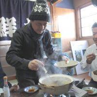 Shared fare: Shigesato Itoi (center) dines with the Saito family, who are rebuilding their fish-processing firm in Kesennuma, Miyagi Prefecture. | HOBO NIKKAN ITOI SHINBUN