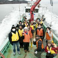 Team spirit rules the waves: Shigesato Itoi (left, wearing a mask) and his wife, actress Kanako Higuchi (behind him) in February among 'Hobonichi' staff and people from tsunami-devastated Kesennuma, Miyagi Prefecuture, aboard a boat owned by an oyster-cultivating firm that is helping to revive the area. | HOBO NIKKAN ITOI SHINBUN