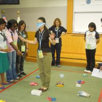 Left: A blindfolded guide is given instructions on how to avoid obstacles by her teammates in an exercise during the leadership training program the same day. | MAMI MARUKO