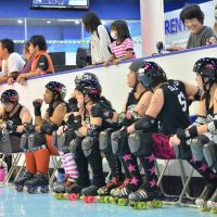 Ready to roll: The Yokota Scary Blossoms (above) watch teammates skate and await the next jam. Roller derby referees are also known as 'Zebras.' The derby pack in position awaiting the approaching Scary Blossoms' jammer. | MARINA BEHRENDT PHOTOS