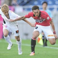 J. League action: Kazuya Murata (left) of Cerezo Osaka and Urawa Reds' Tomoaki Makino attempt to swap shirts mid-match during a J. League clash in October. | KYODO
