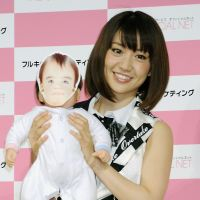 AKB48's Yuko Oshima holds a doll at a press conference for an Internet Service Provider, which features a computer program that lets fans see what a baby between them and their favorite member of AKB48 might look like. | KYODO