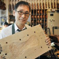 From the rubble: Violinist Muneyuki Nakazawa holds a piece of wood that he eventually hopes to refashion into a musical instrument. The violin maker uses driftwood that he found among debris from the tsunami that struck the Tohoku Region on March 11, 2011. | KYODO