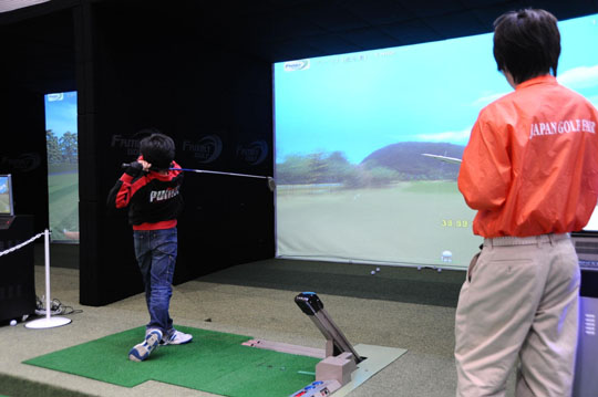 Taking a swing: A boy practices virtual golf at last year's Japan Golf Fair.
