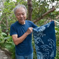Dyed-in-the-hemp: Masanao Shiroma holds up a finished piece of aizome — Ryukyu-ai indigo dyed hemp — in the grounds of Aikaze, near the Motobu region in Okinawa. | STEPHEN MANSFIELD PHOTOS