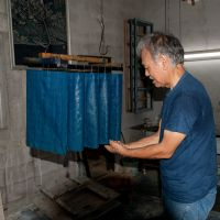 True blue: Indigo-dyed fabrics are hung inside Masanao Shiroma's workshop. The dye used is derived from Ryukyu-ai plants, hand-picked  from the Yanbaru Forest of Okinawa.