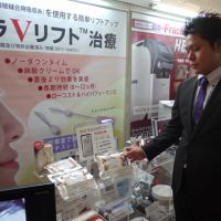 Beyond skin deep: A salesman at the 35th annual meeting of the Japan Society of Aesthetic Plastic Surgery on Oct. 11-12 showcases a Korean thread face-lift, which he says revitalizes facial skin and smoothes out wrinkles. | TOMOKO OTAKE