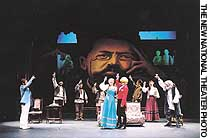 The cast of 'The Sneeze' performs 'The Proposal' against a backdrop portrait of the dramatist, Anton Chekhov.