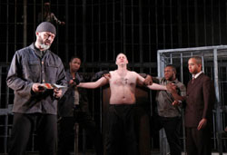 Not so tasty: At an impromptu court convened in a prison named Venice, Shylock (Richard Clothier) cuts flesh from the body of Antonio (Bob Barrett) to repay his loan.