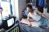Sitting on a platform bed in a hotel room that doubles as a shop, a Chinese merchant of Korean ancestry watches a Seoul TV station in Ussurisk (above); a Chinese farmer stands proudly before his watermelon field near Birobidzhan, Russia (below).