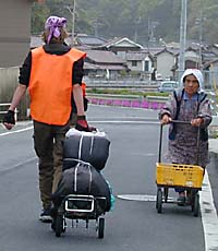 Mary hauls her 26-kg load through a small town on the long and winding road from Hokkaido to the Land of Mu, while an old lady pushes her trolley toward  a less-distant destination.