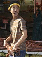 In the Morning Market, a stallholder gets a grip on a crab