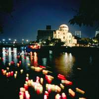 Lanterns float down a river in memory of victims of the first atomic bomb dropped on Japan by the United States; the monument to Sadako Sasaki with paper cranes in the background. Sadako dies from radiation poisoning 10 years after America dropped the bomb on Hiroshima.