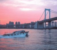 A boat chugs toward the Rainbow Bridge in Minato Ward at dawn. | KIT NAGAMURA PHOTOS