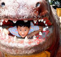 A child lies inside a concrete dinosaur in a niche park