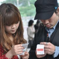 People read new-year omikushi (fortune-telling notes) bought at Naminoue Shrine in Naha.