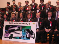 Charged ions: Keio University professor Hiroshi Shimizu (third from right, front row) and other founders of SIM-Drive Corp. line up Wednesday in Yokohama to announce the firm's new project to develop a lighter electric vehicle. | HIROKO NAKATA