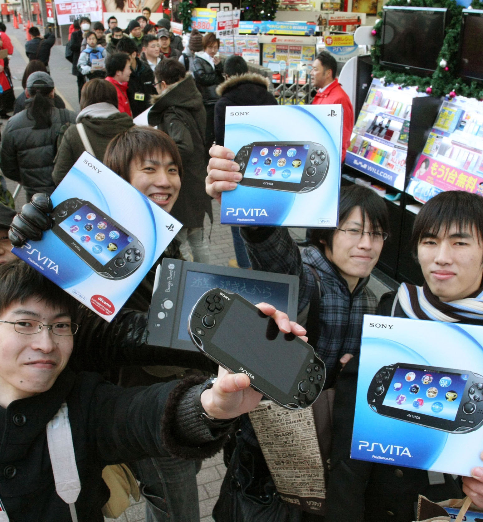 La dolce vita: Game enthusiasts show off Sony's new PlayStation Vita consoles they purchased at a Tokyo store on Dec. 17, the first day the hand-held players went on sale. | KYODO