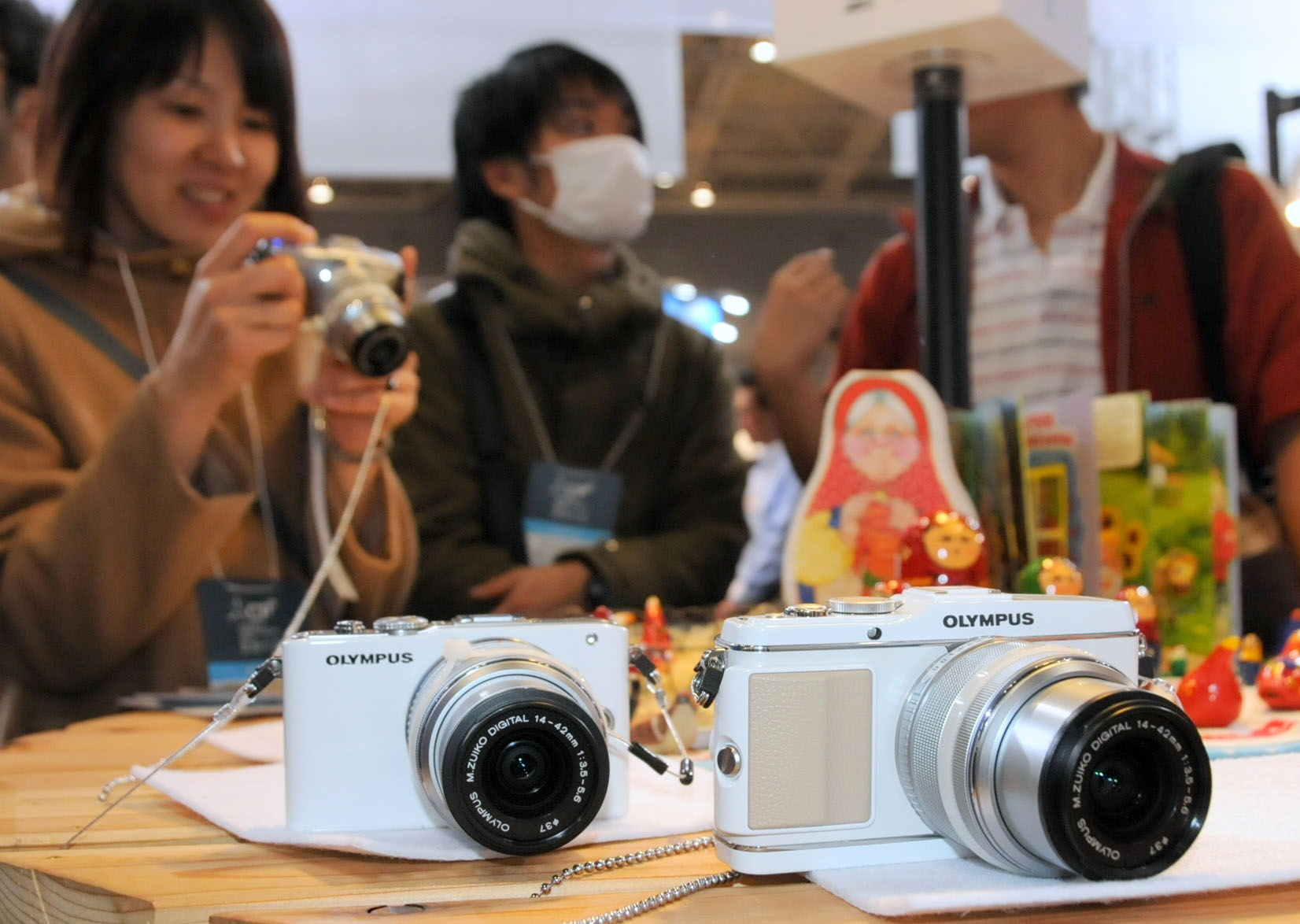 Viewfinder: A visitor tries out an Olympus Corp.'s Pen mirrorless digital camera featuring interchangeable lenses at CP+2012, the country's largest camera show, which kicked off Thursday at Pacifico in Yokohama. | SATOKO KAWASAKI