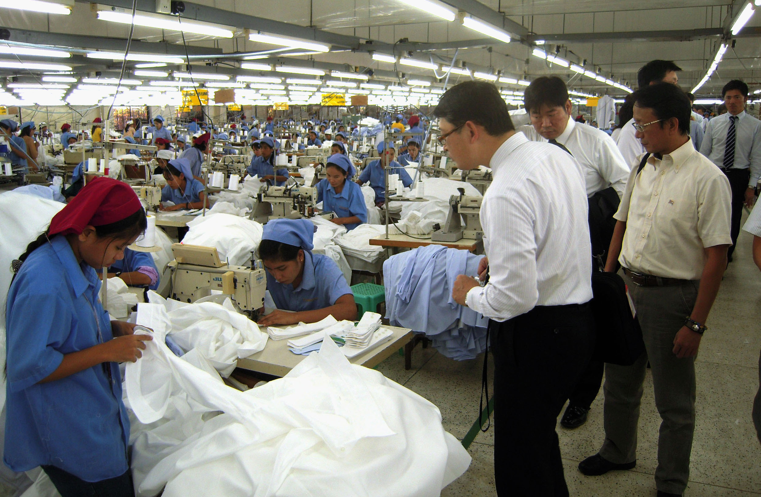 Sewed up: Japanese businessmen tour a sewing plant in the Mingaladon Industrial Park in Yangon in December. | KYODO