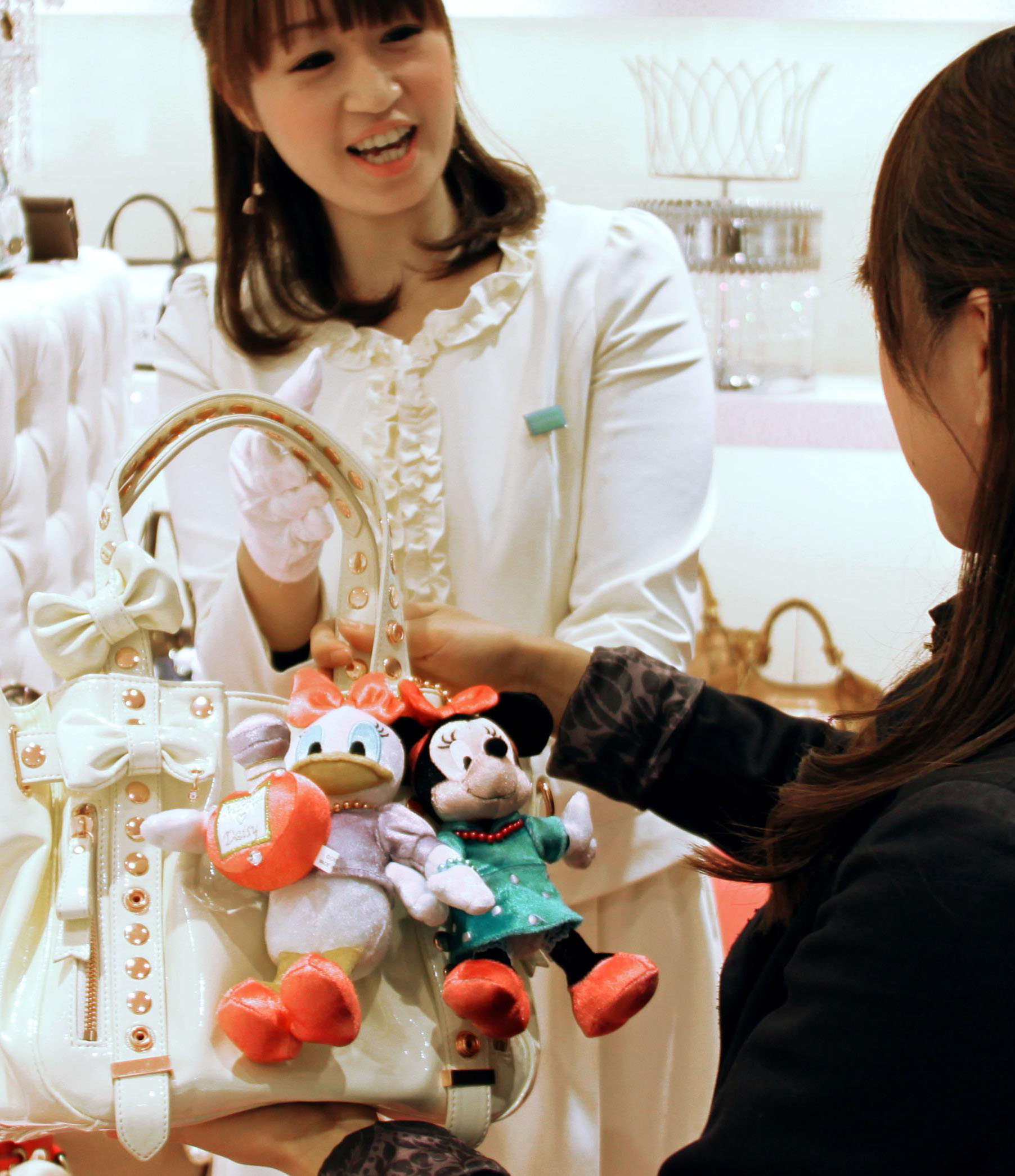 Not too Goofy: A customer checks out a bag for adults adorned with Disney characters at a Samantha Thavasa shop in Tokyo's Omotesando district earlier this month. | KYODO