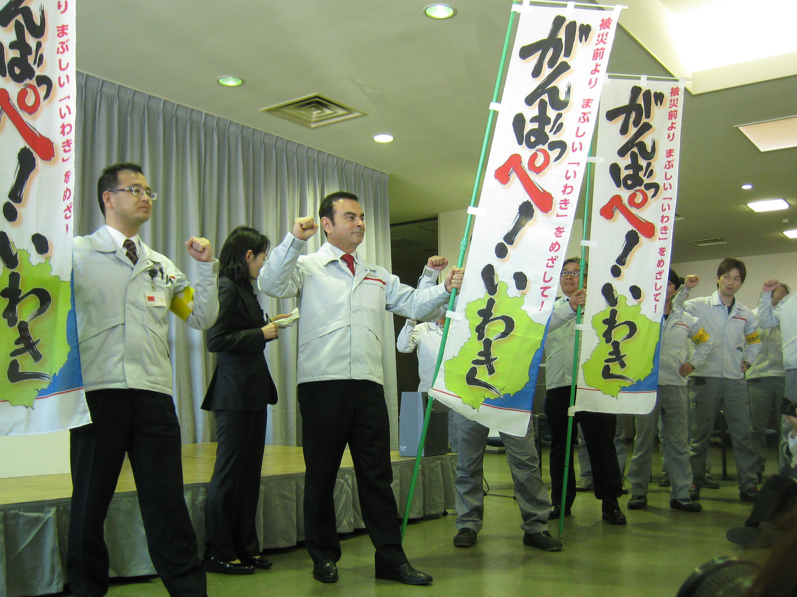 Fighting spirit: Nissan Chief Executive Officer Carlos Ghosn gets ready to shout 'Stick to it! Iwaki' in the Fukushima dialect with plant workers last month. | HIROKO NAKATA