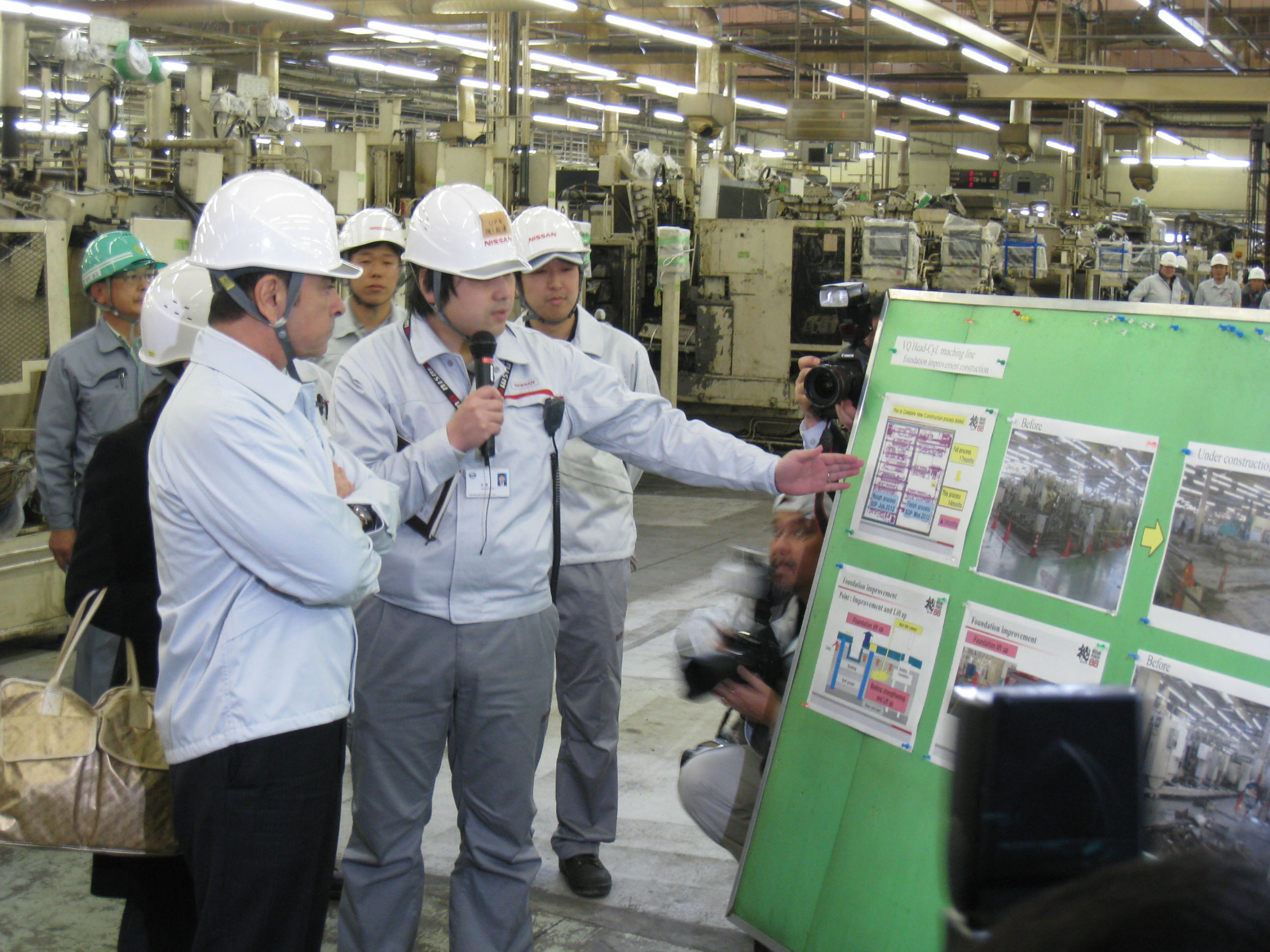 Ghosn listens to a worker's explanation about the renovation schedule for the Iwaki engine plant. | HIROKO NAKATA