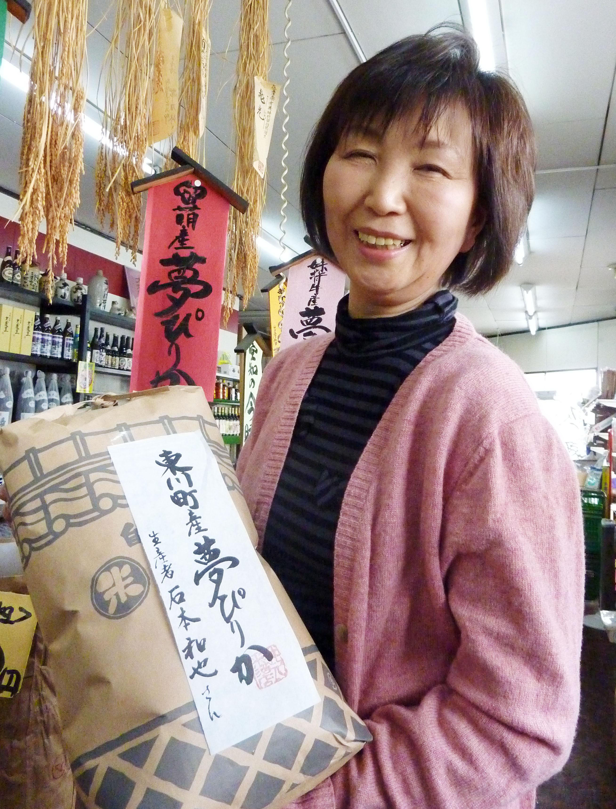 Top grade: The manager of a Sapporo rice shop holds a bag of Yumepirika rice, produced in Hokkaido, on Monday. | KYODO
