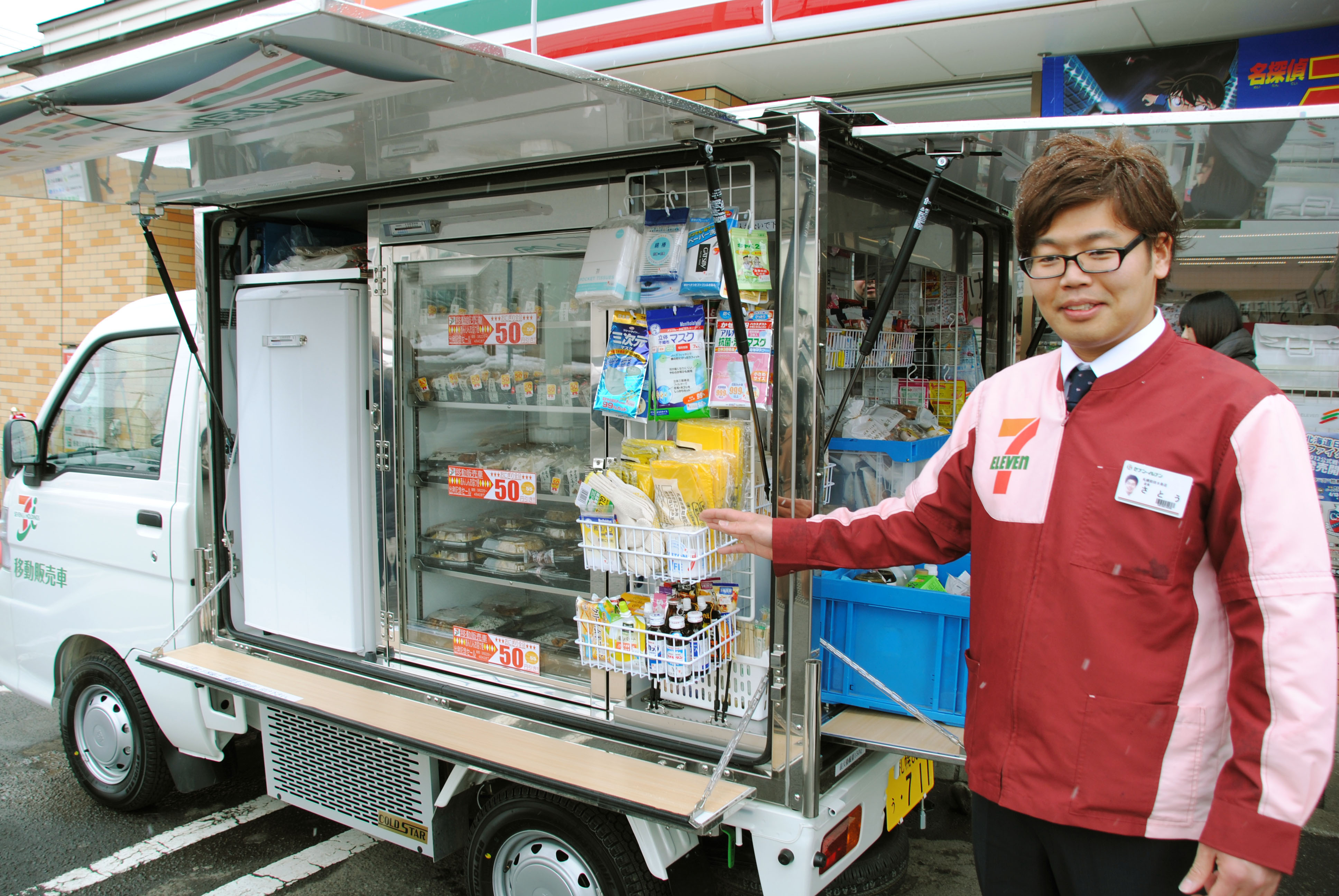 Calling on customers: A 7-Eleven employee shows items sold from its mobile store in Sapporo on March 22, when the chain launched the service there. | KYODO