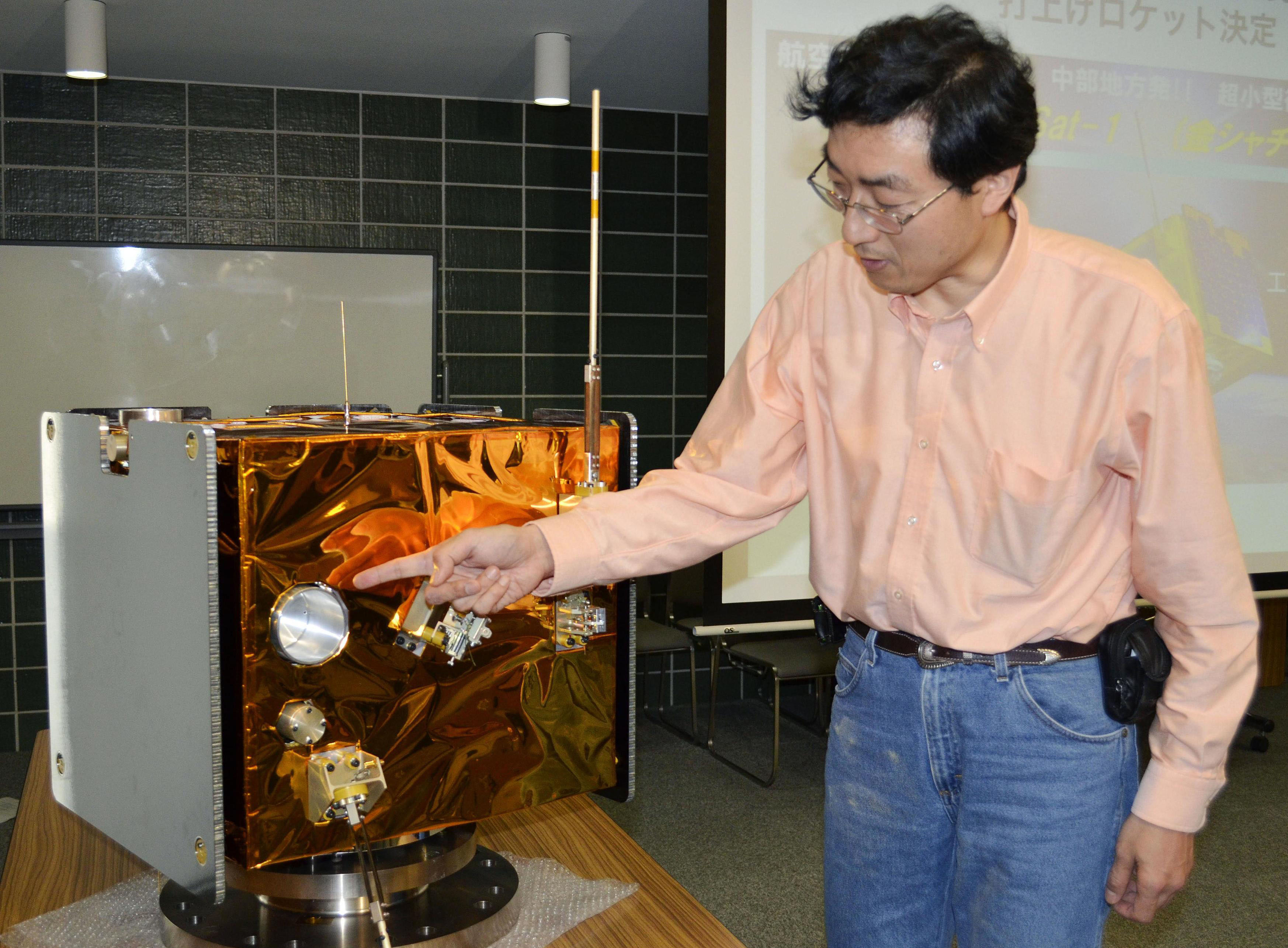 Space cube: Hiroyasu Tajima, a professor at the Solar-Terrestrial Environment Laboratory at Nagoya University, gives a briefing Wednesday about a prototype ChubuSat-1 satellite in Nagoya. | KYODO