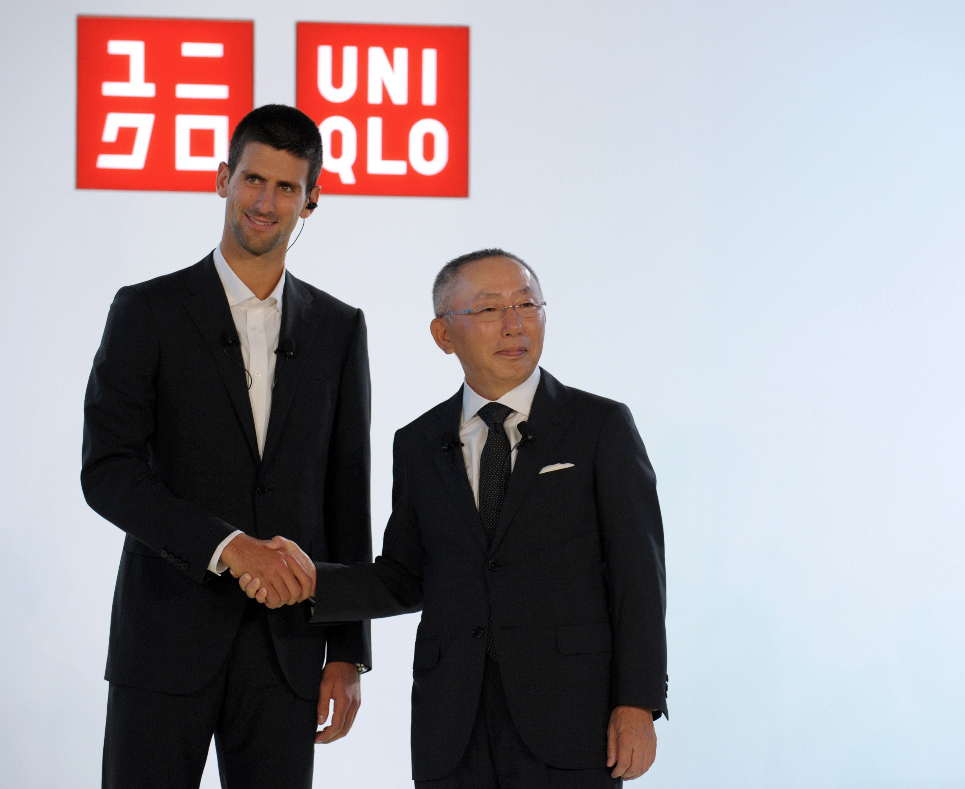 Grand slam: Fast Retailing group and Uniqlo Co. CEO Tadashi Yanai faces reporters Wednesday in Paris with Serbian tennis champion Novak Djokovic, the new face for the clothing brand. | AFP-JIJI