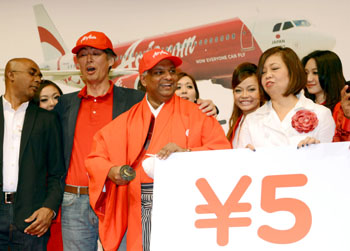 Slice the price: AirAsia group CEO Tony Fernandes holds a sword while the carrier's president, Kazuyuki Iwakata, stands next to him Thursday at a Tokyo news conference to announce new flight services in Japan. | AFP-JIJI
